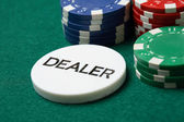 Dealer button and poker chips on a green — Stock Photo
