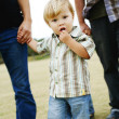 Child walking with parents in a park. — Stock Photo