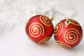 Red Christmas baubles on a glass table. — Stock Photo
