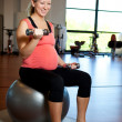 Stock Photo: Pregnant womexercising with weights