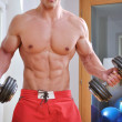 Powerful muscular man lifting weights - Stock Photo