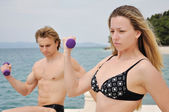 Young students lifting weights on the beach — Stockfoto