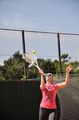 Mladá žena hraje tenis — Stock fotografie
