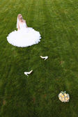 Bride sitting on the grass — Stock Photo