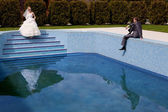 Bride and groom at the pool — Stock Photo