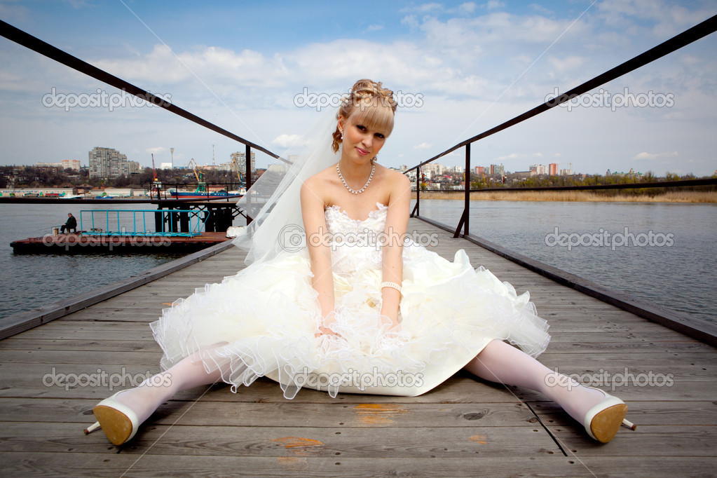 A young girl in a wedding dress sitting on a wooden pier — Stock Photo #3253602