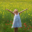 Girl surrounded by rapeseed flowers — Stock Photo