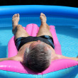 Older man sunbathing in pool — Stock Photo