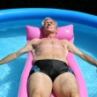 Stock Photo: Older msunbathing in pool