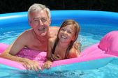 Grandfather and granddaughter on a lilo — Stock Photo