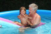 Granddaughter and grandfather on a lilo — Stock Photo