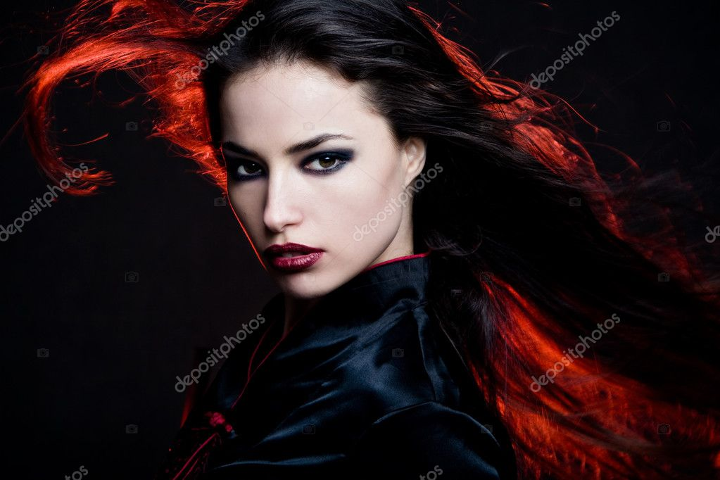 Beautiful brunette woman portrait with hair in motion and red back light, studio shot — Stock Photo #3095774