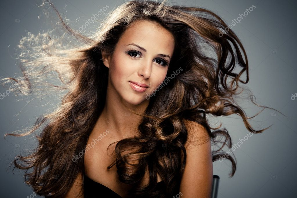 Young brunette  woman with long flying hair, studio shot  Photo #3520861