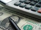 Dollar bill,calculator and pen — Stock Photo