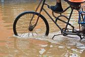 Bike riding through flooded streets — Stock Photo