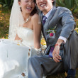 Smiling bride and groom sitting (2) — Stock Photo