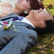 Bride and groom lying on ground — Stock Photo