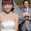 Smiling bride with groom in back (2) — Stock Photo