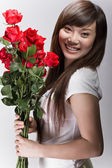 Big smile on asian girl with roses — Stock Photo