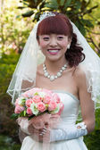 Smiling happy bride with bouquet — Stock Photo