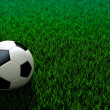 Soccer ball standing on grass field — Stock Photo