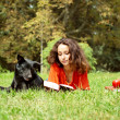 The girl and dog lying on a grass in park — Stok fotoğraf