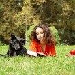 The girl and dog lying on a grass in park — Stockfoto