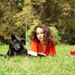 het meisje en de hond liggen op een gras in park — Stockfoto