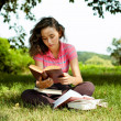 The girl with books sitting on a grass — Stock Photo