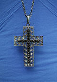 Cross necklace on blue shirt — Стоковое фото