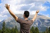 Hombre de pie en la naturaleza con brazos levantado — Foto de Stock