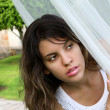 Attractive young woman hiding behind curtain veil — Stock Photo