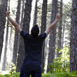 Royalty-Free Stock Photo: Man celebrating with arms lifted in forest