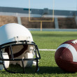 American Football and Helmet on Field - Stock Photo