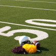 American Football Equipment and Pom Poms on Field - Stock Photo