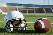 American Football and Helmet on Field — Stock Photo