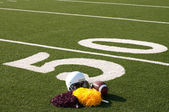 American Football Equipment and Pom Poms on Field — Stock Photo