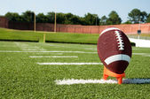 Closeup of American Football on Tee on Field — Stock Photo