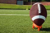 Closeup of American Football on Tee on Field — Stock Photo