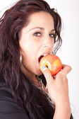 Woman bites in a apple — Stock Photo