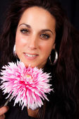 Beautiful brunette and a pink flower — Stock Photo