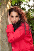 Brunette is leaning against a tree — Stock Photo