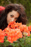 Beautiful brunette is smelling flowers — Stock Photo