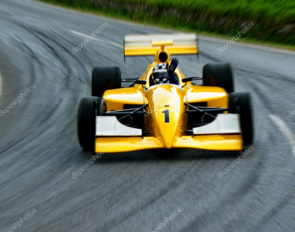 A  yellow car the formula one in movement on road.  — Stock Photo #3227115