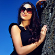 Glamoure lady in black dress next to a tree. - Stock Photo