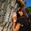 Close up of charming lady in glasses next to a tree. — Stock Photo