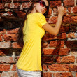 Charming lady in yellow dress next to old wall. — Photo