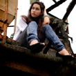 Stock Photo: Beautiful girl sitting in old factory.