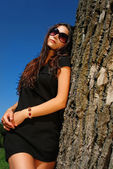 Glamoure lady in black dress next to a tree. — Stock Photo