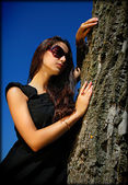 Charming lady in black next to a tree. — Stock Photo
